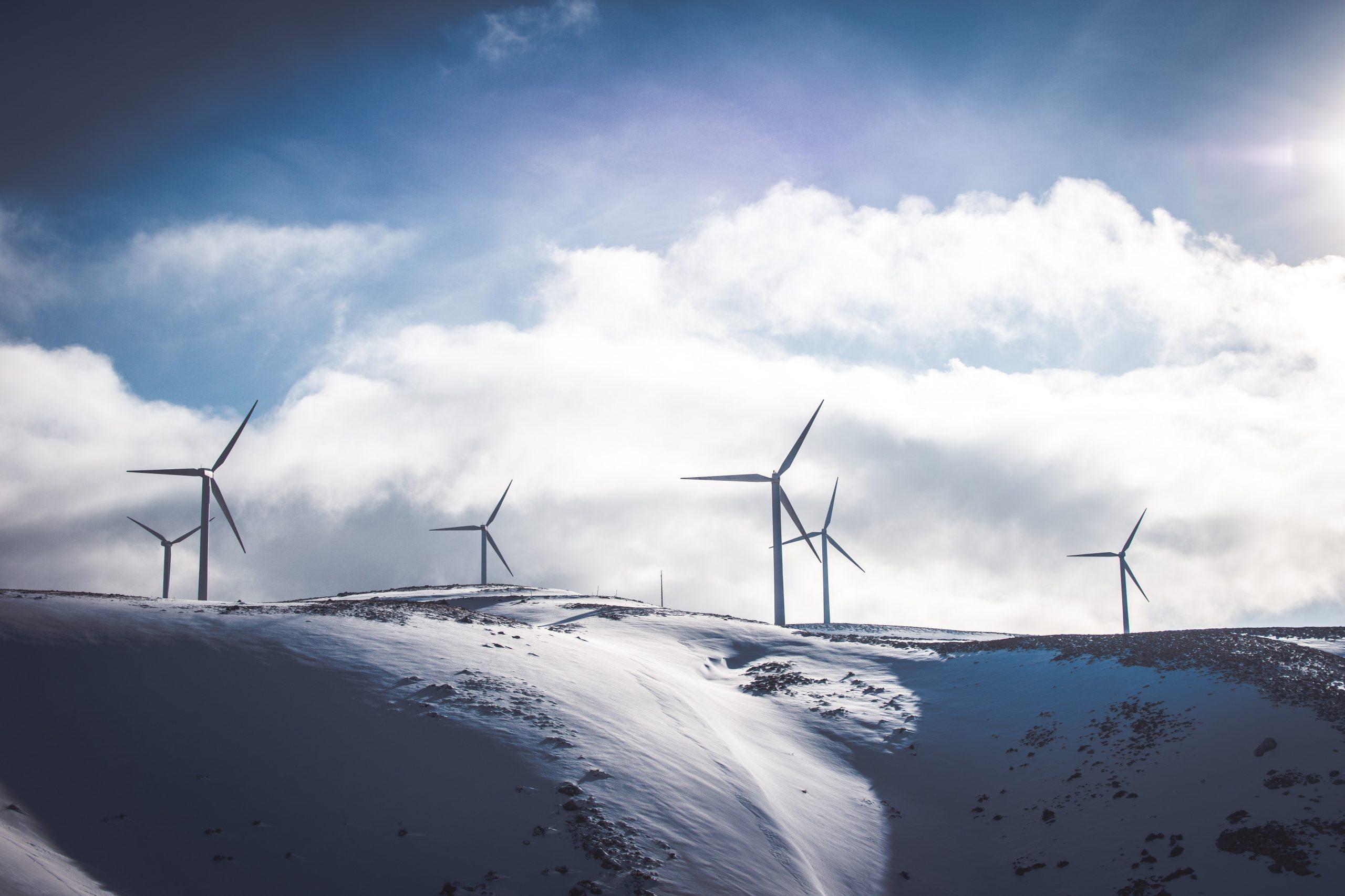 wind turbines on snow covered hills